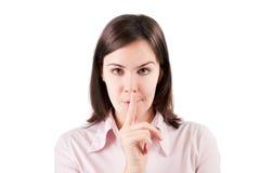 Mujer de negocios joven que hace el gesto del silencio aislado sobre blanco. Imagen de archivo