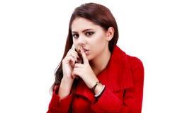 Mujer de negocios joven que hace gesto del silencio durante llamada de teléfono Imagenes de archivo