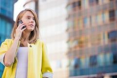 Mujer de negocios joven que hace una llamada de teléfono en su teléfono elegante Fotografía de archivo