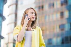 Mujer de negocios joven que hace una llamada de teléfono en su teléfono elegante Fotos de archivo