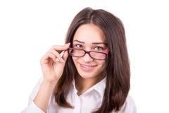 Mujer de negocios joven que mira sobre los vidrios Fotos de archivo