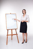 Mujer de negocios joven que muestra algo en el fondo blanco Imagen de archivo libre de regalías