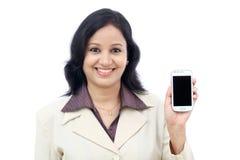 Mujer de negocios joven que muestra con la exhibición negra del teléfono móvil Fotos de archivo