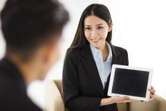 Mujer de negocios joven que muestra la tableta en blanco en oficina imagenes de archivo