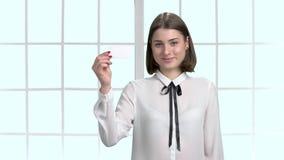 Mujer de negocios joven que muestra la tarjeta en blanco metrajes