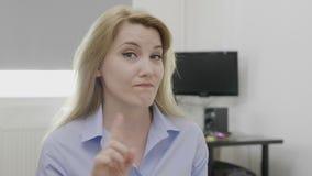 Mujer de negocios joven que no muestra a desacuerdo con la negativa ningún gesto con oferta decreciente del finger en su oficina  almacen de metraje de vídeo