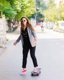 Mujer de negocios joven que patina en el tablero patinador Imágenes de archivo libres de regalías