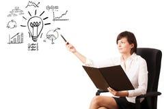Mujer de negocios joven que presenta la bombilla con los diversos diagramas Foto de archivo