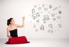 Mujer de negocios joven que presenta medios iconos dibujados mano Imagen de archivo libre de regalías