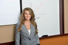 Mujer de negocios joven que se coloca delante de carta de las ventas Foto de archivo libre de regalías