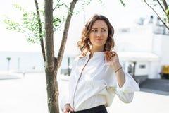 Mujer de negocios joven que se coloca en la calle fotografía de archivo