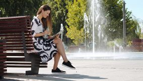Mujer de negocios joven que se sienta en un agua potable del banco y que trabaja en la tableta