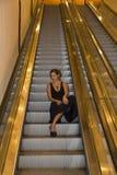 Mujer de negocios joven que se sienta en una escalera móvil imágenes de archivo libres de regalías