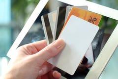 Mujer de negocios joven que sostiene tarjetas de crédito O que hace compras en línea Imagen de archivo