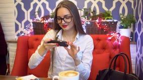 Mujer de negocios joven que toma la foto de la comida con el teléfono móvil que se sienta en café mujer que fotografía la comida  metrajes