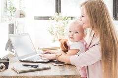 Mujer de negocios joven que trabaja en casa detrás del ordenador portátil con un pequeño niño Espacio de trabajo escandinavo crea fotos de archivo