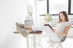 Mujer de negocios joven que trabaja en casa y que lee un libro con sus piernas en la tabla Estilo escandinavo creativo imagen de archivo