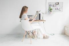 Mujer de negocios joven que trabaja en casa y que lee un libro Espacio de trabajo escandinavo creativo del estilo imágenes de archivo libres de regalías