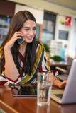 Mujer de negocios joven que trabaja en el café, usando el teléfono elegante Foto de archivo