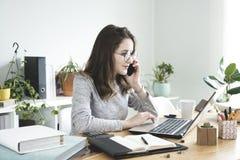 Mujer de negocios joven que trabaja en el ordenador portátil y el teléfono móvil que habla en oficina fotografía de archivo libre de regalías