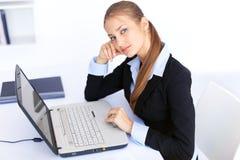 Mujer de negocios joven que trabaja en la computadora portátil en oficina Fotos de archivo