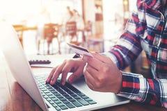 mujer de negocios joven que trabaja en su ordenador portátil y que usa la tarjeta de crédito que se sienta en la tabla de madera  Foto de archivo