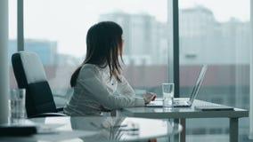 Mujer de negocios joven que trabaja en un ordenador portátil en oficina moderna ella que sonríe y toma una rotura almacen de video