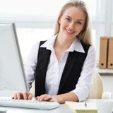Mujer de negocios joven que usa el ordenador en la oficina fotos de archivo