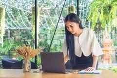 Mujer de negocios joven que usa el ordenador portátil con informe del documento en el café fotografía de archivo libre de regalías