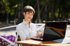 Mujer de negocios joven que usa el ordenador portátil en el café de la acera Imagen de archivo libre de regalías