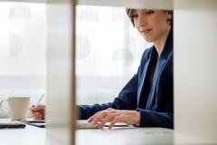 Mujer de negocios joven que usa la calculadora foto de archivo libre de regalías