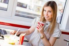 Mujer de negocios joven rubia hermosa que bebe un cóctel que mira la cámara y que trabaja en el ordenador portátil Fotografía de archivo libre de regalías