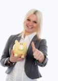 Mujer de negocios joven sonriente con la hucha y el pulgar para arriba Foto de archivo