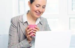 Mujer de negocios joven sonriente con la taza usando la computadora portátil Imagenes de archivo