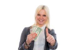 Mujer de negocios joven sonriente con los dólares y el pulgar para arriba Foto de archivo libre de regalías