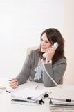 Mujer de negocios joven sonriente en el teléfono en la oficina imágenes de archivo libres de regalías