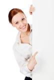 Mujer de negocios joven sonriente feliz con un letrero en blanco Imágenes de archivo libres de regalías