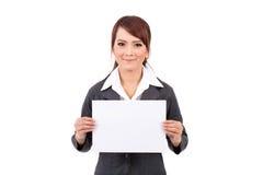 Mujer de negocios joven sonriente feliz que sostiene el letrero en blanco Imagen de archivo