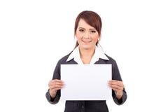 Mujer de negocios joven sonriente feliz que sostiene el letrero en blanco Foto de archivo