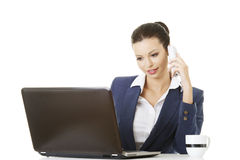 Mujer de negocios joven sonriente que habla en el teléfono Foto de archivo libre de regalías