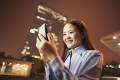 Mujer de negocios joven sonriente que mira su teléfono móvil afuera la noche Fotografía de archivo