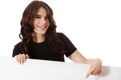 Mujer de negocios joven sonriente que sostiene el letrero en blanco Foto de archivo
