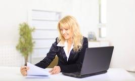 Mujer de negocios joven sonriente que usa la computadora portátil en el trabajo Fotografía de archivo