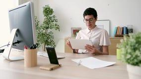 Mujer de negocios joven sonriente usando su tableta digital mientras que trabaja en la oficina almacen de video