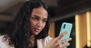 Mujer de negocios joven usando el teléfono móvil en la cafetería acogedora Ella mensajes de la ojeada en línea y textos de contes metrajes