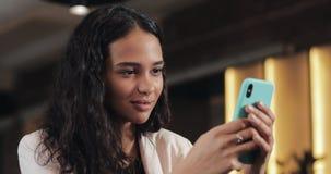 Mujer de negocios joven usando el teléfono móvil en la cafetería acogedora Ella mensajes de la ojeada en línea y textos de contes almacen de video
