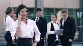 Mujer de negocios justo-pelada bonita que tiene una llamada de teléfono y sus compañeros de trabajo que hablan en el fondo metrajes