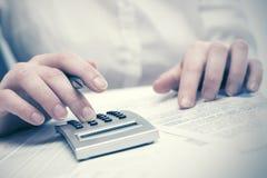 Mujer de negocios de la contabilidad financiera que usa la calculadora imagen de archivo libre de regalías