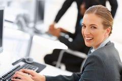 Mujer de negocios linda que trabaja en el ordenador Fotografía de archivo libre de regalías