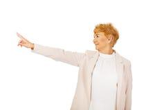 Mujer de negocios mayor de la sonrisa que señala para el copyspace o algo Foto de archivo libre de regalías